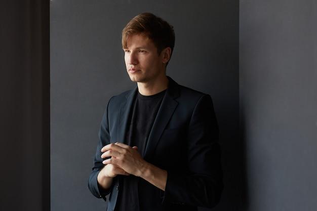 Ritratto di profilo di un bel giovane uomo d'affari in giacca, su sfondo grigio. vista orizzontale.