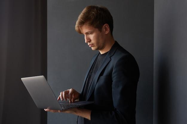 Ritratto di profilo di un bel giovane uomo d'affari in giacca, che tiene in mano un computer portatile, su sfondo nero.