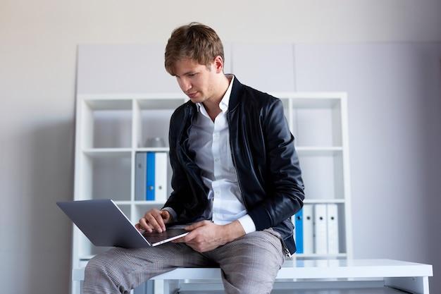 Ritratto di profilo di un bel giovane seduto sul tavolo in ufficio che lavora al suo computer portatile.