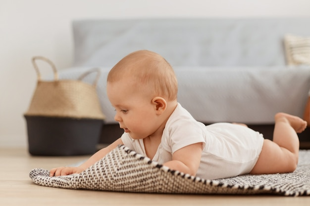 Ritratto di profilo di una piccola neonata che indossa una tuta bianca sdraiata sul tappeto sul pavimento, impara a gattonare a casa in un soggiorno luminoso e accogliente, il bambino gioca da solo mentre è sdraiato sulla pancia.