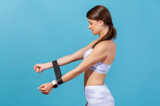 Ritratto di profilo donna atletica motivata che fa sport, pompando i muscoli delle mani con un espansore di gomma