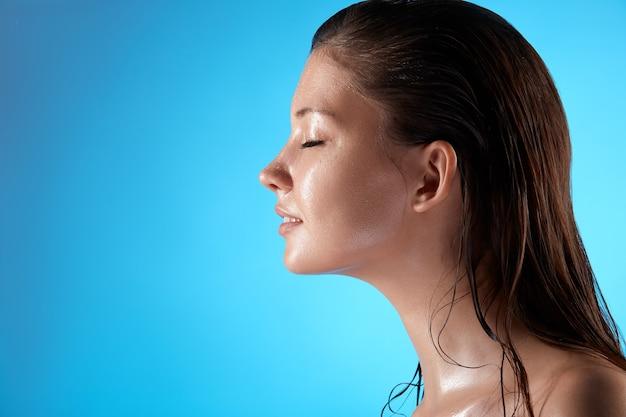 Ritratto di profilo di bella ragazza con la faccia bagnata isolata sull'azzurro