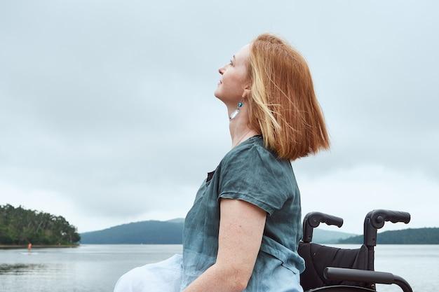 Ritratto di profilo della donna rossa in sedia a rotelle che gode della vista naturale.