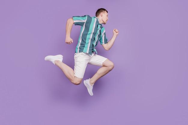 Il ritratto di profilo di un ragazzo sportivo energico salta la corsa sembra uno spazio vuoto su sfondo viola