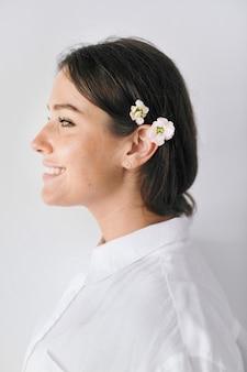 Ritratto di profilo di una donna che indossa fiori tra i capelli