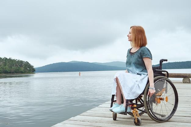 Ritratto di profilo di una donna su sedia a rotelle che cammina lungo la passerella godendo di una splendida vista sulla baia del mare sea