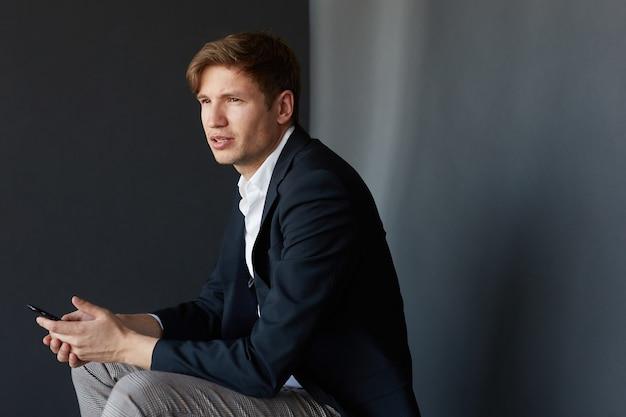 Ritratto di profilo di un giovane uomo d'affari in tuta seduto e tenendo tra le mani un telefono cellulare, su sfondo nero.