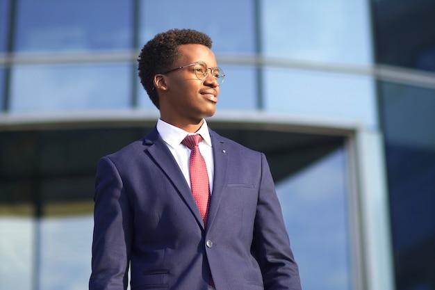 Ritratto di profilo di giovane imprenditore fiducioso di successo felice in abito formale, cravatta e occhiali all'aperto edificio aziendale. uomo bello afroamericano africano nero, sorridente di impiegato
