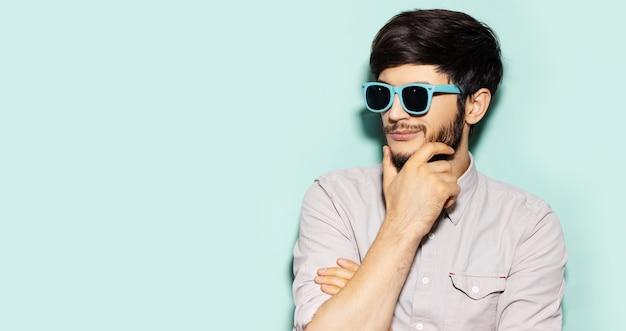 Ritratto di profilo di giovane ragazzo premuroso che indossa occhiali da sole ciano