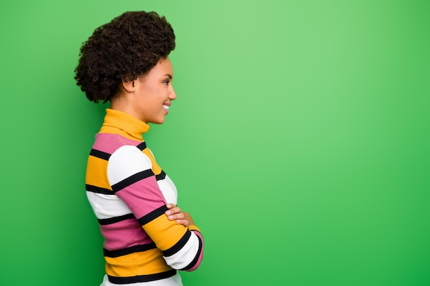 Profilo della signora riccia della pelle scura graziosa di affari braccia incrociate alla ricerca di uno spazio vuoto operaio amichevole responsabile indossare maglione a righe casual