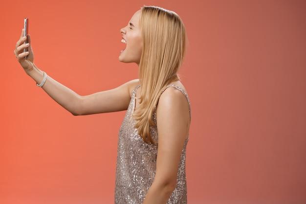 Profilo girato divertente spensierata donna bionda tenere smartphone sollevato bocca aperta ampia urlando registrazione video proprio grido urlo, in piedi vestito glamour argento vicino a sfondo rosso sciocco intorno.