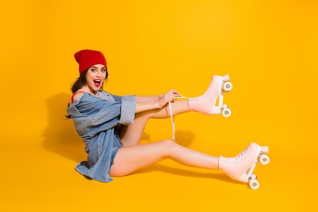 Pattini a rotelle dei lacci delle scarpe del legame della ragazza pazza del lato di profilo impressionato