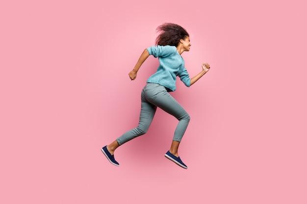 Profilo lato figura intera dimensione del corpo foto di allegro casual carino giovane che aspira a venire per le vendite in tempo saltando in esecuzione in pantaloni grigi scarpe maglione blu isolato muro di colore pastello