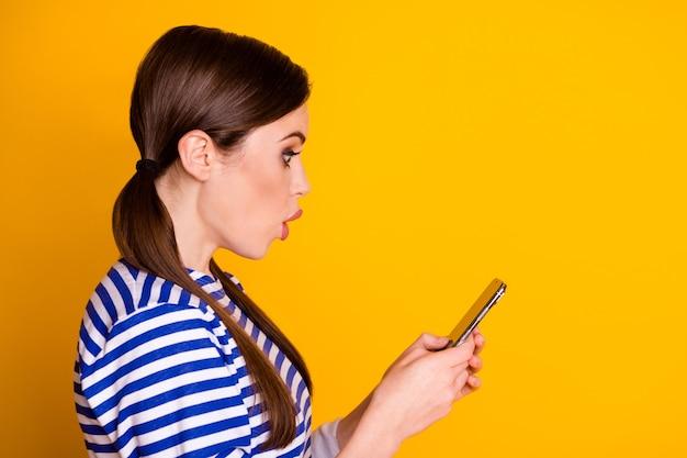 La foto laterale del profilo della ragazza stupita usa il cellulare impressionato leggere le informazioni sulla pandemia del virus corona dei social media indossare abiti di bell'aspetto isolato sfondo di colore brillante