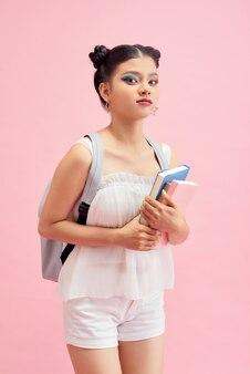 La foto a lato del profilo di una ragazza positiva tiene i libri di copia andare a piedi in aula lezione lezione biblioteca isolata su sfondo rosa