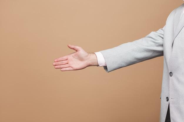 Primo piano di vista laterale di profilo dell'uomo d'affari in vestito grigio chiaro che sta e che dà la mano di saluto. girato in studio al coperto, isolato su sfondo marrone chiaro.