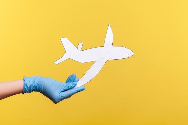 Primo piano di vista laterale di profilo della mano umana in guanti chirurgici blu che tengono la carta dell'aeroplano.