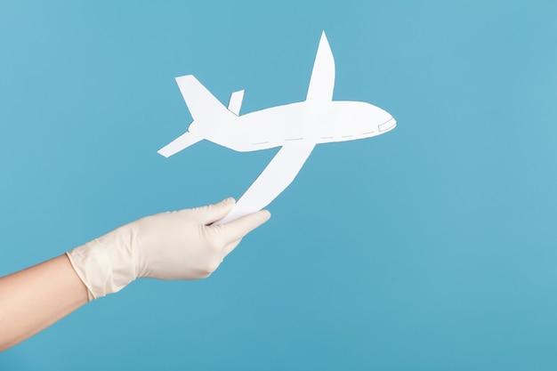 Primo piano di vista laterale di profilo della mano umana in guanti chirurgici bianchi che tengono la carta dell'aeroplano.