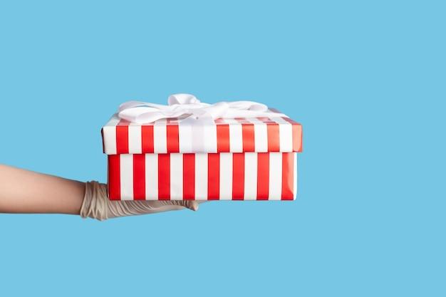 Primo piano di vista laterale di profilo della mano umana in guanti chirurgici bianchi che tengono scatola regalo a strisce bianche rosse.