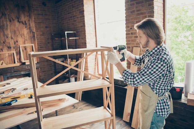 Vista laterale di profilo di artigiano barbuto concentrato in posa nella sua falegnameria