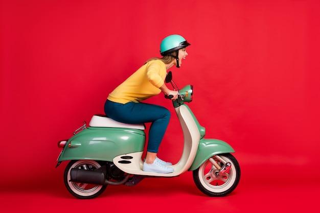 Ritratto di vista laterale di profilo della bocca aperta del ciclomotore di guida della ragazza sbadata pazza sulla parete rossa