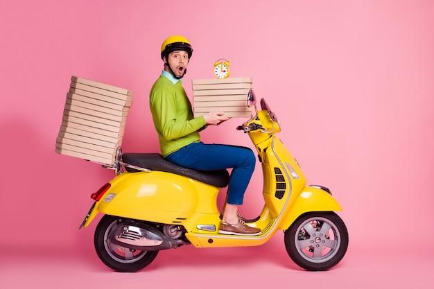Ritratto di vista laterale di profilo del ragazzo che guida il ciclomotore che porta le scatole della torta