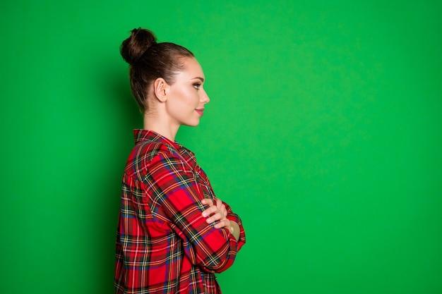 Profilo vista laterale ritratto di lei bella attraente abbastanza calma pacifica allegra ragazza che indossa camicia a quadri con le braccia piegate salone di bellezza isolato su sfondo di colore verde brillante brillante brillantezza vibrante