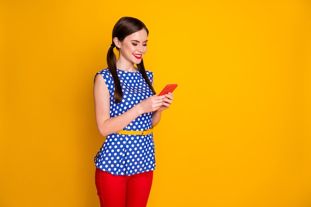 Profilo vista laterale ritratto di lei bella attraente piuttosto concentrata ragazza allegra utilizzando dispositivo app condivisione multimediale multimediale isolato brillante vivido brillantezza vibrante colore giallo sfondo