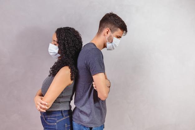 Profilo vista laterale ritratto del suo lui lei lei ha offeso malato malato malsano indisposto coppia braccia conserte indossando maschera di garza di sicurezza mers cov distanza sociale