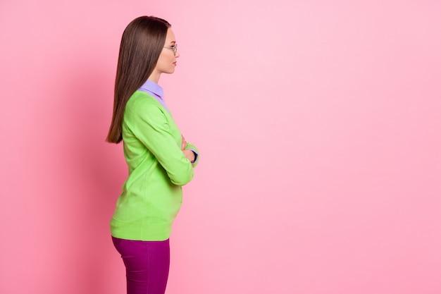Profilo vista laterale ritratto di bella ragazza attraente contenuto serio braccia piegate copia spazio posto isolato su sfondo rosa color pastello