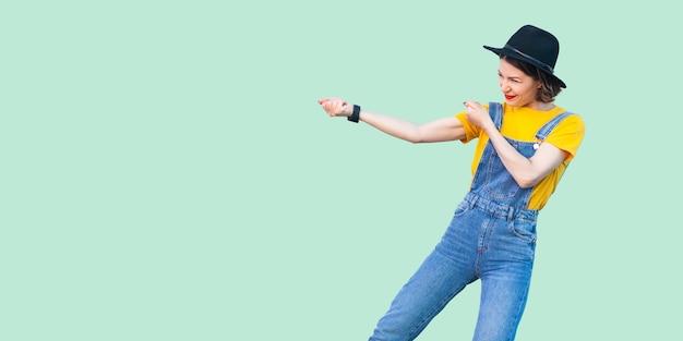 Profilo vista laterale ritratto di una ragazza hipster piuttosto giovane in tuta di jeans blu, camicia gialla e cappello nero in piedi con pugno o gesto di trazione. studio al coperto colpo isolato su sfondo verde chiaro.