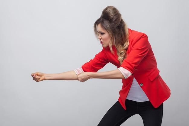 Ritratto di vista laterale del profilo di una bella donna d'affari seria con acconciatura e trucco in blazer rosso fantasia, in piedi e cercando di tirare. girato in studio al coperto, isolato su sfondo grigio.