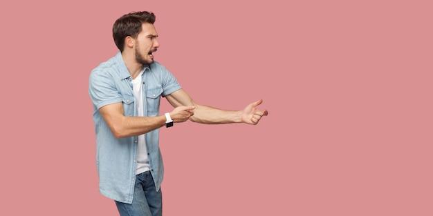 Profilo vista laterale ritratto di un giovane uomo barbuto urlante serio in camicia casual blu in piedi in attacco o tirando le mani gesto e guardando avanti. girato in studio al coperto, isolato su sfondo rosa.