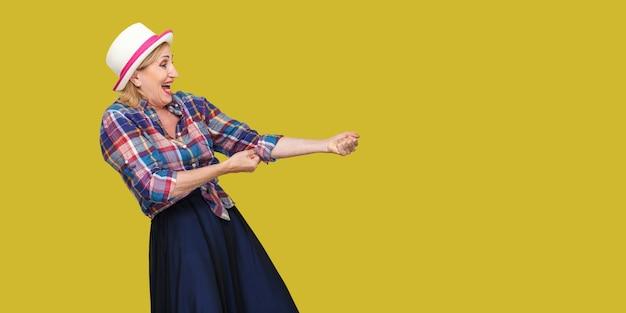 Ritratto di vista laterale del profilo di una donna matura elegante e seria in stile casual con cappello in piedi in modalità di attacco o che fa un gesto di trazione di qualcosa. studio al coperto colpo isolato su sfondo giallo.