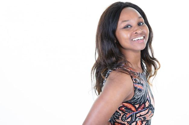 Profilo di una donna africana sorridente della bella giovane donna dalla pelle scura con lo spazio in bianco della copia vuoto Foto Premium