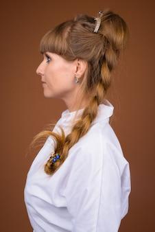 Vista di profilo di bella bionda imprenditrice con i capelli intrecciati