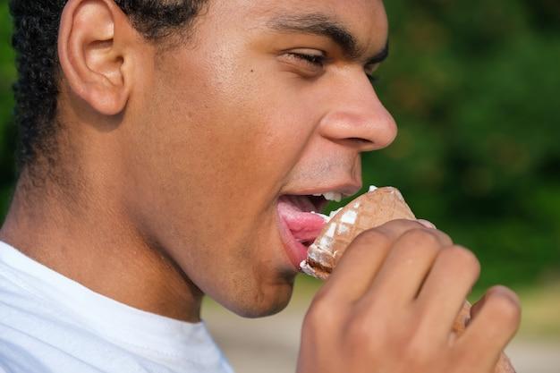 Ritratto del primo piano di vista di profilo di un uomo afroamericano felice che gode del gelato all'aperto.