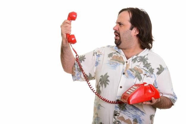Vista di profilo dell'uomo caucasico grasso che tiene vecchio telefono che sembra arrabbiato