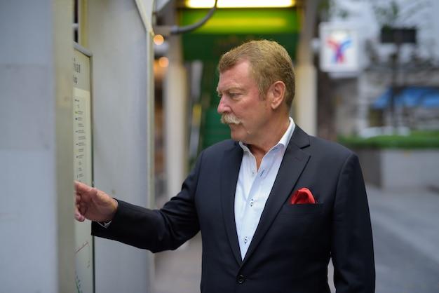 Vista di profilo di uomo d'affari senior bello con i baffi controllando la mappa della città