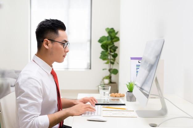 Vista di profilo di un bel giovane che fa alcuni esercizi di meditazione mentre lavora in ufficio
