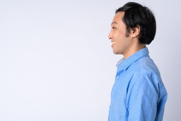 Vista di profilo dell'uomo d'affari giapponese felice che sorride contro il bianco