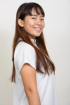 Vista di profilo di felice giovane donna asiatica guardando la fotocamera
