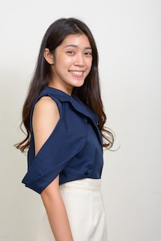 Vista di profilo di felice giovane bella asiatica imprenditrice guardando la fotocamera