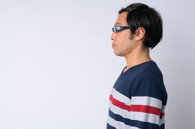 Vista di profilo dell'uomo giapponese contro uno sfondo bianco
