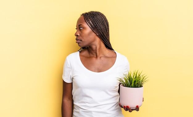 Nella vista di profilo cercando di copiare lo spazio in avanti, pensando, immaginando o sognando ad occhi aperti tenendo un vaso per piante