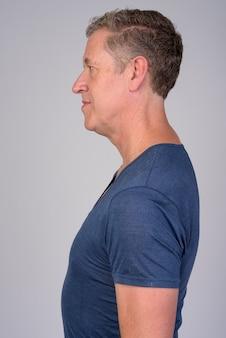 Vista di profilo di un uomo maturo contro uno sfondo bianco