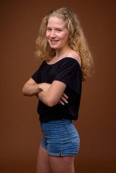 Ritratto di vista di profilo di giovane bella ragazza adolescente bionda sorridente