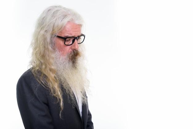 Vista di profilo di uomo d'affari barbuto senior triste guardando verso il basso