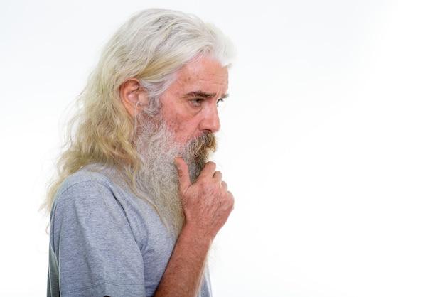 Vista di profilo dell'uomo barbuto anziano che pensa con la mano sul mento