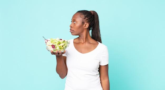 Nella vista di profilo pensare, immaginare o sognare ad occhi aperti e tenere in mano un'insalata